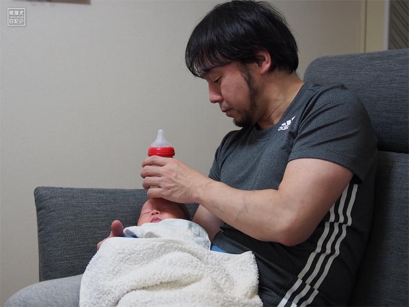 赤ん坊のおでこに哺乳瓶